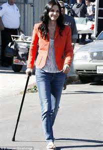 Courteney Cox hobbles along with a walking stick following